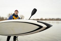 Happy senior man with paddleboard. Happy and smiling senior paddler mid 60s with his stand up paddleboard on a lake shote after paddling workout, early spring stock images