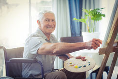 Happy senior man painting at home Stock Image