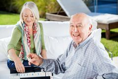 Happy Senior Man Playing Rummy With Woman Stock Photography