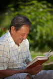 Happy senior man reading. Happy senior man is his late 70s sitting in garden at home and reading book, smiling Stock Image