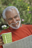 Happy Senior Man Reading Newspaper Stock Images