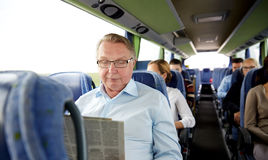 Happy senior man reading newspaper in travel bus Stock Image