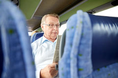 Happy senior man reading newspaper in travel bus Stock Photography