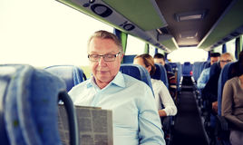 Happy senior man reading newspaper in travel bus Stock Photos