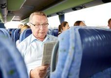 Happy senior man reading newspaper in travel bus Royalty Free Stock Photo