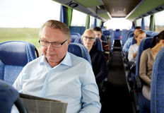 Happy senior man reading newspaper in travel bus. Transport, tourism, trip and people concept - senior men reading newspaper in travel bus Stock Images