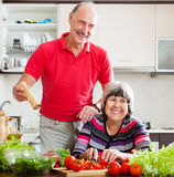 Happy senior man in red and  woman cooking  together Stock Photography