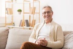 Happy senior man resting on sofa and looking at camera royalty free stock photo