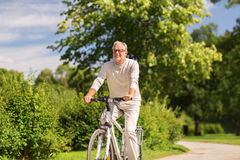 Happy senior man riding bicycle at summer park. Active old age, people and lifestyle concept - happy senior man riding fixie bicycle at summer park royalty free stock photos