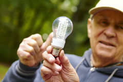 Senior man showing eco diode bulb Royalty Free Stock Photos