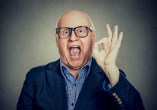 Happy senior man showing ok sign. Portrait of a happy senior man showing ok sign isolated on gray wall background royalty free stock photography