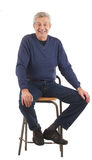 Happy senior man sits with hands on knees. Happy senior man smiles, seated with hands on knees. Dark blue jeans and long sleeved shirt. Isolated on white royalty free stock photography