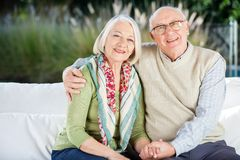 Happy Senior Man Sitting With Arm Around Woman On Stock Photography