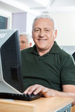 Happy Senior Man Sitting In Computer Classroom Royalty Free Stock Images
