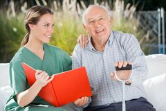 Happy Senior Man Sitting By Female Nurse Holding Royalty Free Stock Photo