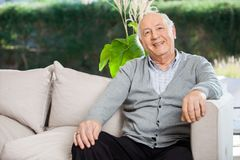 Happy Senior Man Sitting At Nursing Home Porch Royalty Free Stock Image