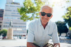 Happy senior man sitting outdoors in the city Stock Images