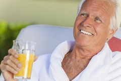 Senior Man In Bathrobe Drinking Orange Juice Royalty Free Stock Image