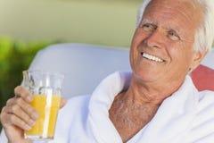 Senior Man In Bathrobe Drinking Orange Juice. Happy senior man sitting outside wearing bathrobes at a health spa drinking orange juice royalty free stock image