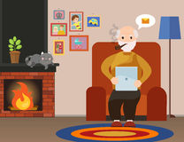 Happy senior man sitting on the sofa read book on tablet Royalty Free Stock Images