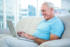 Happy senior man sitting on sofa while using laptop Stock Images