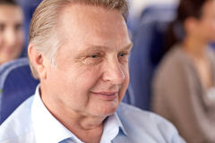Happy senior man sitting in travel bus or airplane Stock Images