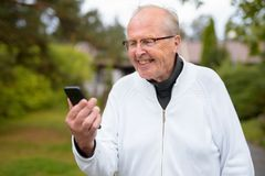 Happy Senior Man Smiling While Using Phone At Home Outdoors. Portrait of senior man wearing eyeglasses at home outdoors stock photos