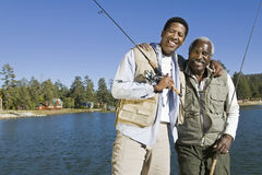 Happy Senior Man And Son With Fishing Rods By Lake. Portrait of happy senior men and adult son holding fishing rods by lake Royalty Free Stock Images