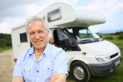 Happy senior man standing by camping car Stock Image