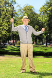 Happy senior man standing and gesturing happiness in park Stock Image