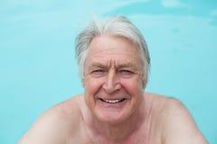 Happy senior man swimming in pool Stock Image