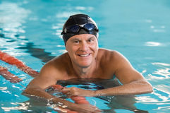 Happy senior man swimming. Smiling senior man standing in pool holding rope. Portrait of mature man wearing swim cap and goggles looking at camera. Proud and Stock Images