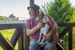 Senior man taking his lovely basenji dog and watching both while sitting on summer veranda. Happy senior man taking his lovely basenji dog and watching both royalty free stock images