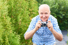 Happy Senior Man Taking Pictures in Park. Portrait of smiling senior man taking pictures in park using vintage photo camera while travelling Royalty Free Stock Image