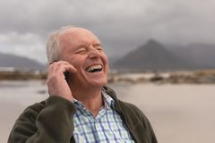 Happy senior man talking on mobile phone at beach royalty free stock image