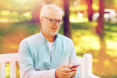 Happy senior man texting on smartphone at summer. Technology, senior people, lifestyle and communication concept - happy old man dialing phone number and texting Royalty Free Stock Photo