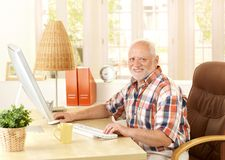 Happy senior man using computer. At home, smiling at camera Royalty Free Stock Images