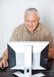 Happy Senior Man Using Computer In Classroom Royalty Free Stock Photo