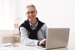 Senior man using computer and looking at camera royalty free stock images