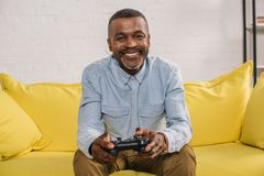 Happy senior man using joystick and smiling. At camera royalty free stock photo