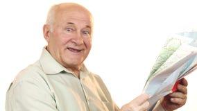 Happy senior man using a map smiling joyfully royalty free stock image