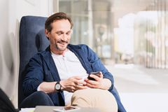 Happy senior man using mobile phone. Portrait of joyful mature businessman messaging on smartphone while relaxing on comfortable armchair. He is looking at Royalty Free Stock Image