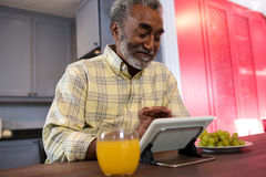 Happy senior man using tablet computer in kitchen. Happy senior man using tablet computer at table in kitchen Royalty Free Stock Photography