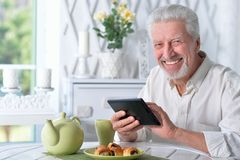 Happy senior man using tablet while drinking tea at kitchen. Portrait of happy senior man using tablet while drinking tea at kitchen Stock Image