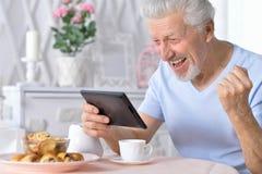 Senior man using tablet while drinking tea. Happy senior man using tablet while drinking tea at kitchen Stock Photos