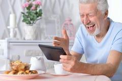 Senior man using tablet while drinking tea. Happy senior man using tablet while drinking tea at kitchen Royalty Free Stock Photos