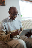 Happy senior man using tablet. While sitting on sofa at home Stock Photos