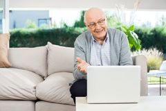 Happy Senior Man Video Chatting On Laptop At Porch Stock Photography