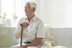 Happy senior man with walking stick relaxing in a nursing house. Concept photo stock images