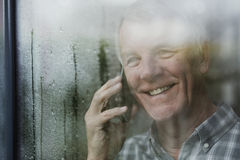 Senior Man Enjoying Phonecall. Happy senior man is watching the rain from his window while talking to someone on the phone Stock Photo